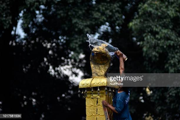 A Nepalese priest cleans to offer milk towards Nag or Sanke God at Nag Pokhari Kathmandu Nepal on Thursday August 16 2018 On the following day Snakes...