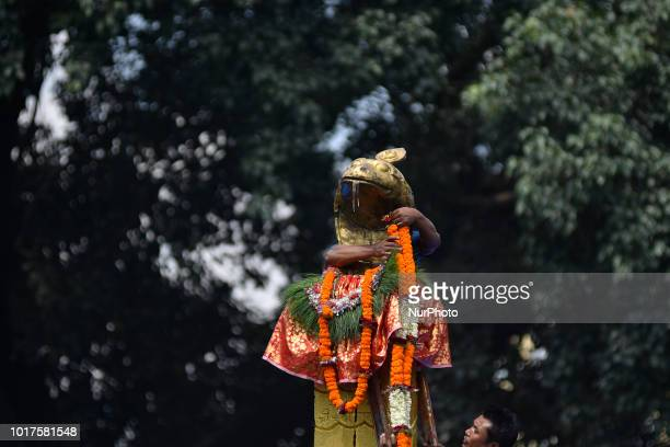 A Nepalese priest decorates after offering milk towards Nag or Sanke God at Nag Pokhari Kathmandu Nepal on Thursday August 16 2018 On the following...
