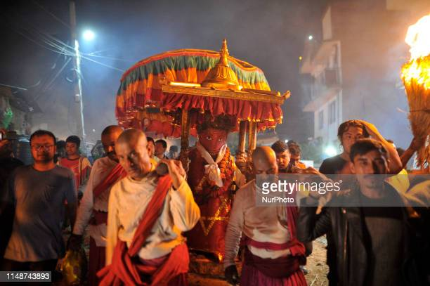 Nepalese Priests carrying idol Rato Machindranath towards Bungamati as devotees fire a traditional straw torch to welcome idol Rato Machindranath in...