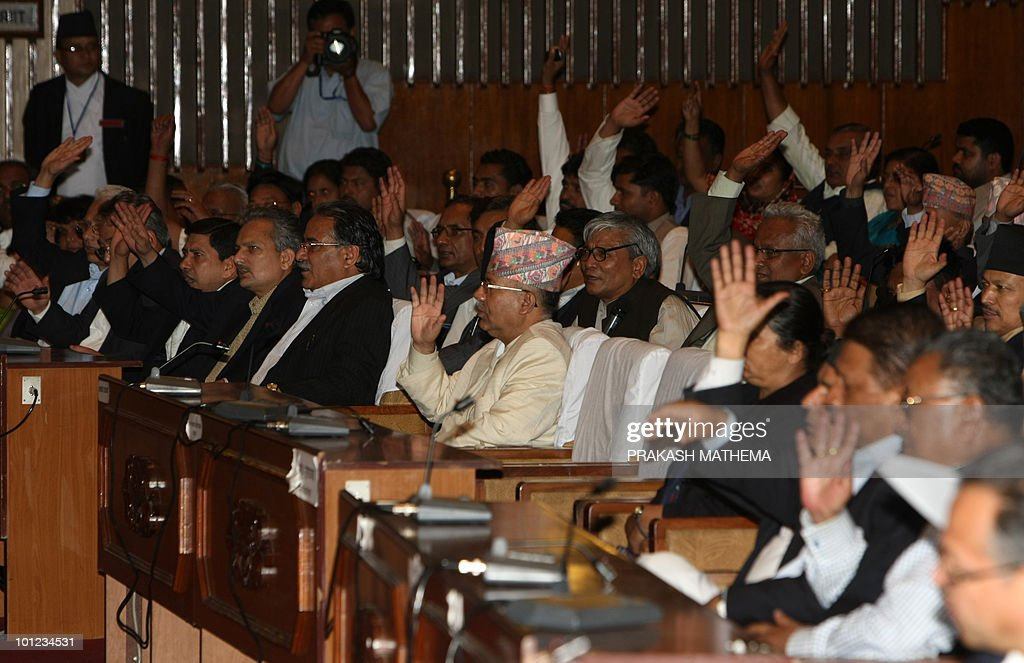 Nepalese Prime Minister Madav Kumar Nepal (C), ministers and lawmakers raise their hand to support extending parliment's term at parliament in Kathmandu on May 28, 2010. Nepal's main party leaders agreed Friday to extend parliament's term, in a dramatic eleventh-hour deal to avert political crisis in the troubled nation.The Maoist party said the leaders had agreed to form a new national consensus government as part of the deal and reports said the prime minister had agreed to resign 'soon', although this could not immediately be confirmed . AFP PHOTO/Prakash MATHEMA