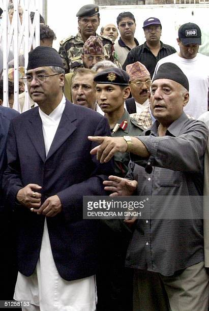 Nepalese Prime Minister Sher Bahadur Deuba listens as a Muslim man points to damage at a mosque in Kathmandu 03 September 2004 as normal Friday...