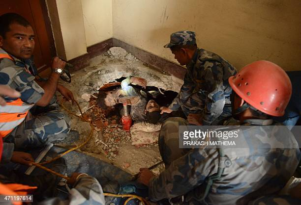 Nepalese rescue personnel help a trapped earthquake survivor as his friend lies dead next to him in Swyambhu in Kathmandu on April 26 2015 Rescuers...