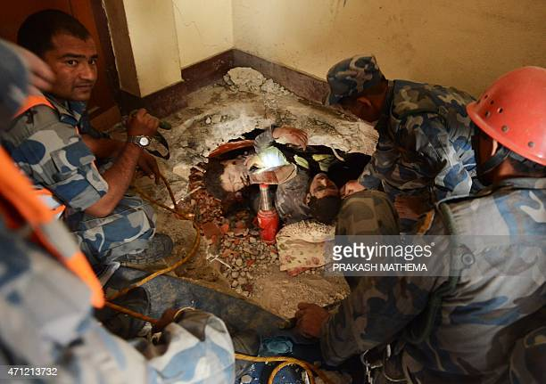 Nepalese rescue personnel rescue a trapped earthquake survivor as his friend lies dead next to him following an earthquake in Swyambhu in Kathmandu...