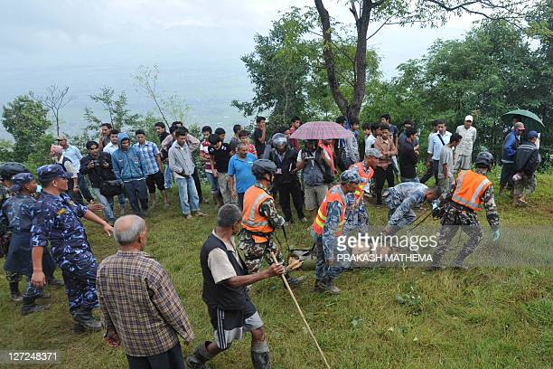 Nepalese rescuers recover the body of a passenger who died when a Buddha Air Beechcraft 1900D aircraft crashed in Lalitpur on the outskirts of...