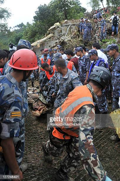 Nepalese rescuers recover the body of a passenger who died when a Buddha Air Beechcraft 1900D aircraft crashed at Kot Danda in Lalitpur on the...
