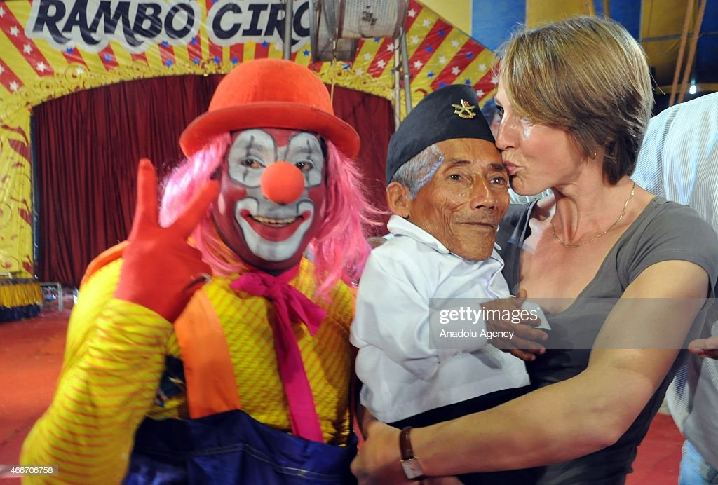 Nepalese resident and world's shortest adult Chandra Bahadur Dangi, 74, (C) poses with a clown during a visit to a circus in Mumbai on March 18, 2015. Dangi, from a remote valley in southwestern Nepal, measuring 54.6 cm (21.5 inches) tall.