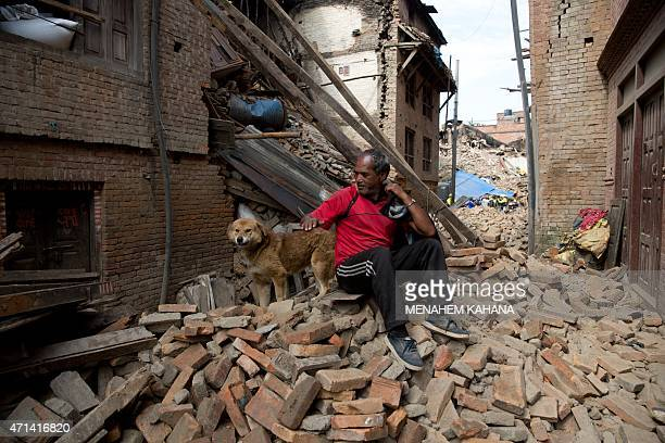A Nepalese resident pats a dog as he sits on rubble in the earthquake damaged area of Bhaktapur on the outskirts of Kathmandu on April 28 2015 Hungry...