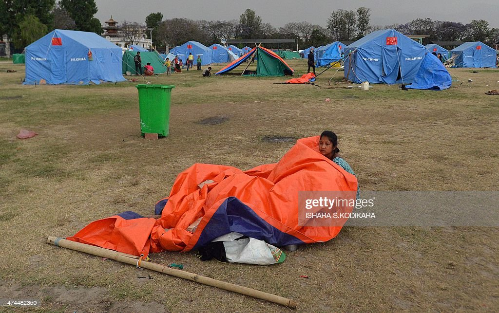 A Nepalese resident sits under a broken tent after heavy winds at a relief c& for & A Nepalese resident sits under a broken tent after heavy winds at ...