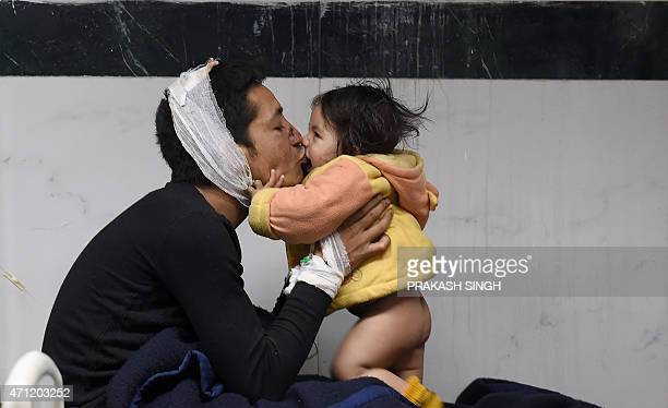 Nepalese resident Suresh Parihar plays with his 8monthold daughter Sandhaya as he is treated for injuries sustained in an earthquake at a city...