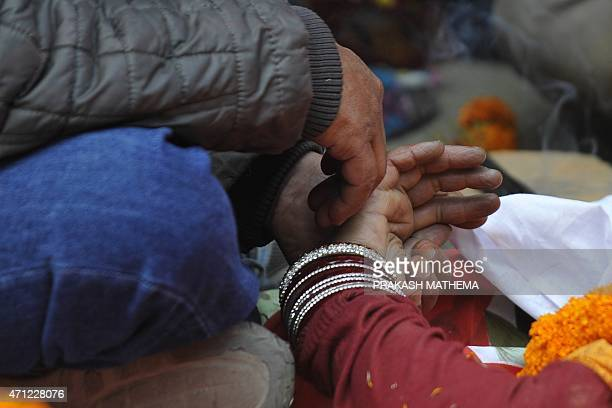 Nepalese residents mourn the death of a relative following an earthquake at a mass cremation at Pashupatinath in Kathmandu on April 26 2015 Aid...