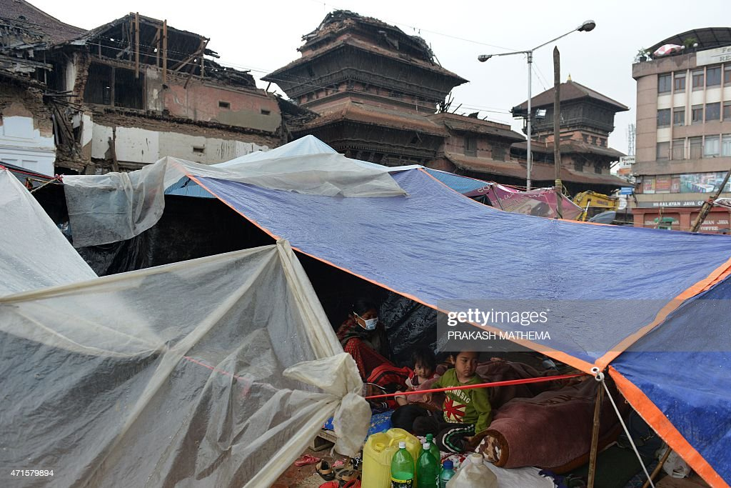 Nepalese residents sit in a makeshift shelter near buildings damaged in an earthquake at Durbar Square at dawn in Kathmandu on April 30, 2015. The UN launched an appeal for Nepalese quake survivors in dire need of shelter, food and medical care April 30 as anger boiled at the government's inability to cope with a disaster that has killed more than 5,000 people.
