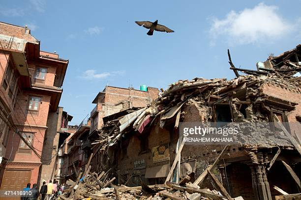 Nepalese residents walk through rubble in the earthquake damaged area of Bhaktapur on the outskirts of Kathmandu on April 28 2015 Hungry and...