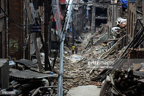 Nepalese residents walks past damaged houses following an earthquake in Bhaktapur on the outskirts of Kathmandu on May 13 2015 Rescuers were battling...
