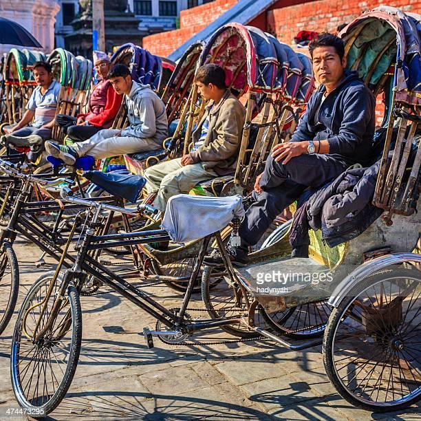 nepalese rickshaws waiting for tourists on durbar square in kathmandu - kathmandu stock pictures, royalty-free photos & images