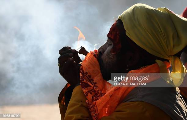 A Nepalese Sadhu smokes marijuana using a chillum a traditional clay pipe as a holy offering for Lord Shiva the Hindu god of creation and destruction...