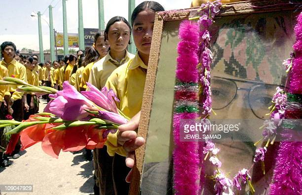 Nepalese school children hold flowers and a photograph of the late King Birendra as they queue in front of the Royal palace to pay respect for the...