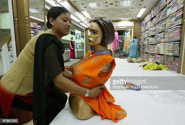 A Nepalese shop worker dresses a mannequin at a shop in Kathmandu 01 May 2006 Daily life in the Nepalese capital is gradually returning to normal as...