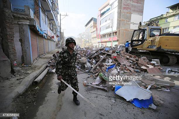 Nepalese soldier walks past the debris of a damaged 5storey building in Balaju neighborhood of Kathmandu after a magnitude 73 earthquake hit Nepal as...