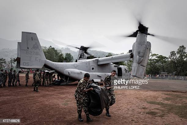 Nepalese soldiers unload relief supplies from an US Osprey aircraft at Dhading Besi some 100 kms north west of Kathmandu on May 9 2015 Following the...