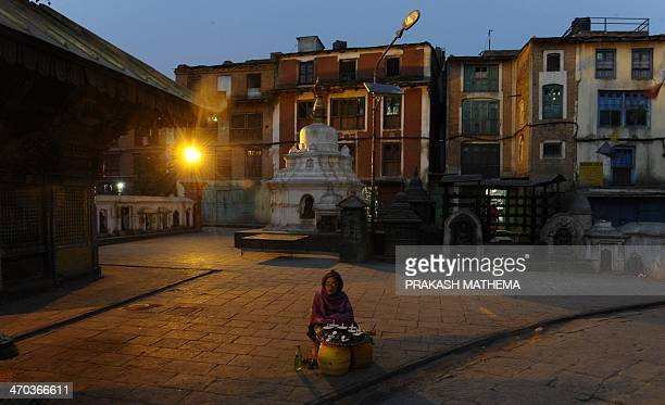 A Nepalese street vendor waits for customers for oil lamps at the Swayambhunath Stupa area in Kathmandu on February 19 2014 The Stupa located west of...