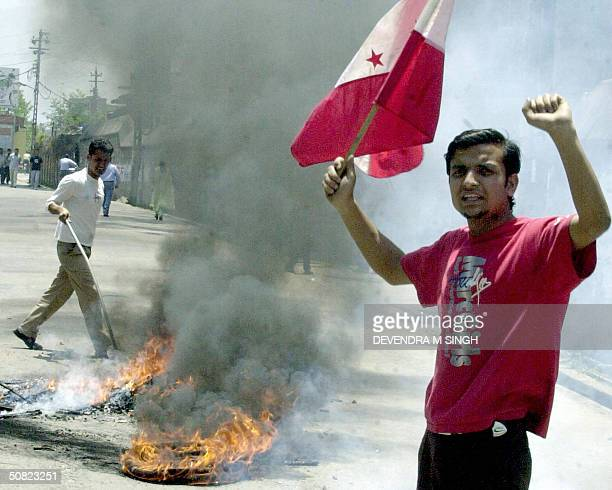 Nepalese student shouts slogans as he waves a flag in front of a pile of burning tyres on the first day of a two day general strike called by an...