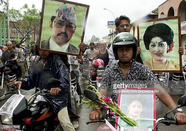 Nepalese supporters of the royal family carry portraits of King Birendra and Queen Aishwarya while riding their motorcycles during a rally in...