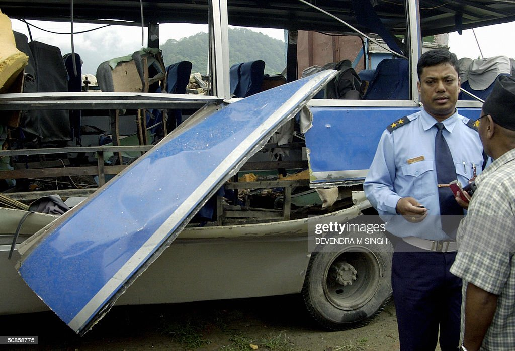 A Nepalese traffic officer (R) speaks with a pedestrian as they stand infront of the wreckage of a bomb dmaged bus in Kathmandu, 20 May 2004. Maoist rebels are suspected of planting the device which exploded on the third day of a nationwide general strike, destroying the bus but injuring no-one.