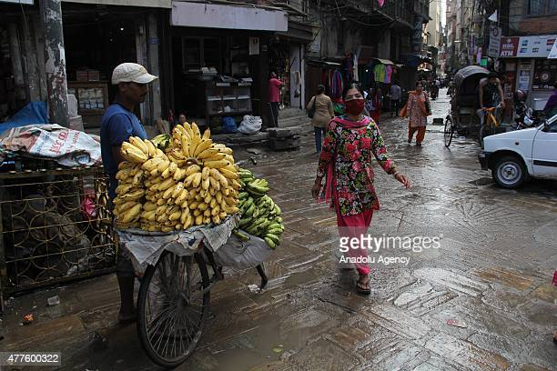 Nepalese vendors are seen at Kathmandu streets in Nepal on June 18 2015 Rubble of buildings hasn't been removed in some areas of Nepal after the...