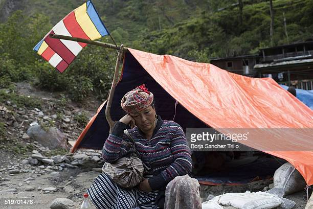 A Nepalese victim of the earthquake sits in front of a makeshift tent as she waits to have dinner on May 01 2015 in Tatopani Nepal The first...