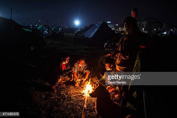 Nepalese victims of the earthquake warm themselves around a bonfire at a makeshift camp at Tunshikel park on April 28, 2015 in Kathmandu, Nepal. A...