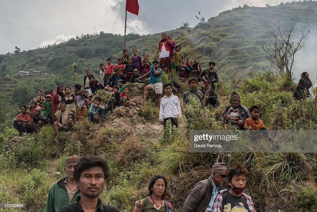 Nepalese villagers look on during an evacuating operation by an Indian helicopter on May 6, 2015 in Lampuk, Nepal. A major 7.9 earthquake hit Kathmandu mid-day on Saturday 25th April, and was followed by multiple aftershocks that triggered avalanches on Mt. Everest that buried mountain climbers in their base camps. Many houses, buildings and temples in the capital were destroyed during the earthquake, leaving over 7000 dead and many more trapped under the debris as emergency rescue workers attempt to clear debris and find survivors. Regular aftershocks have hampered recovery missions as locals, officials and aid workers attempt to recover bodies from the rubble.