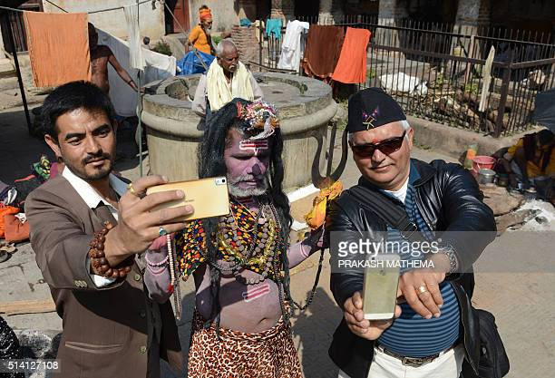 Nepalese visitors take a 'selfie' with a Sadhu dressed as Lord Shiva the Hindu god of creation and destruction near the Pashupatinath Temple during...
