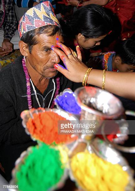 A Nepalese woman applies a fivecolour Tika on her brother's forehead on the occasion of Bhai Tika on the last day of the Hindu festival of Tihar in...