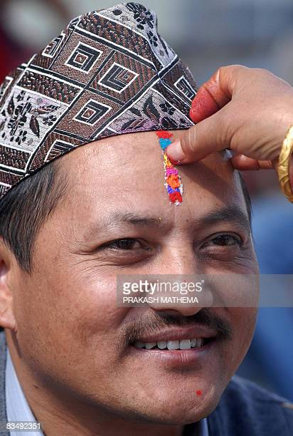 A Nepalese woman applies a sevencolour Tika religious marking to her brother's forehead on the occasion of Bhai Tika brothers' worship on the last...