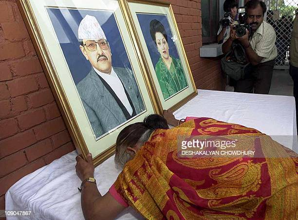 A Nepalese woman breaks down in tears as she grasps a portrait of the late King Birendra displayed at the Royal Palace in Kathmandu 06 June 2001...