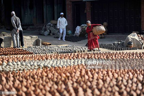 Nepalese woman carries mud pots for drying at Pottery Square in Bhaktapur where small scale traditional pottery making industry are found Bhaktapur...