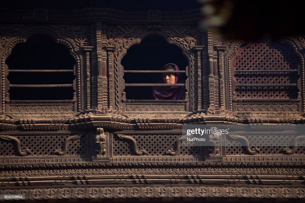 A Nepalese woman glancing from traditinal window at Bhaktapur, Nepal on Friday, January 12, 2018.