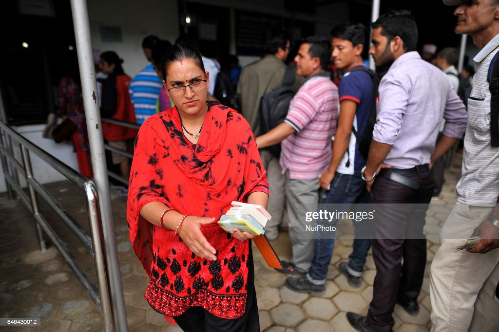 A Nepalese woman holds after exchange new notes for the Biggest Dashain Festival in Kathmandu on Wednesday, September 13, 2017. The central bank said for general public can exchange as much as Rs 27,000 each from its Currency Management Division.