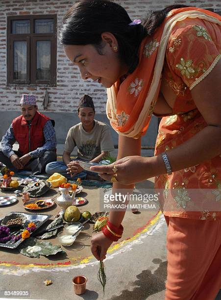 A Nepalese woman pays respects to her brothers on the occasion of Bhai Tika brothers' worship on the last day of the Hindu festival of Tihar in...