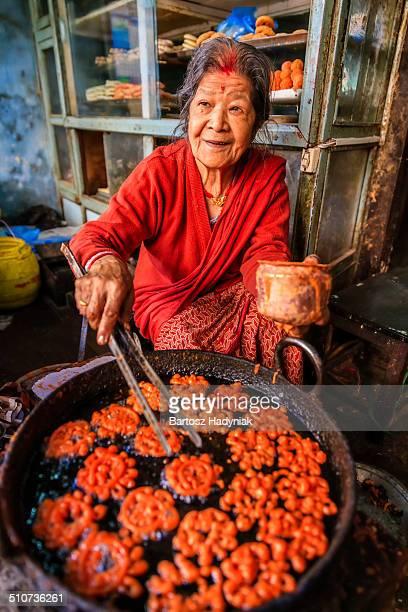 Nepalese woman preparing a sweet - jalebi