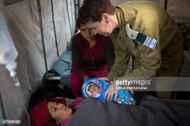 Nepalese woman Quqila Pondari looks at her baby who was born during the night at the Israeli field hospital in Kathmandu on April 30 2015 Quqila...