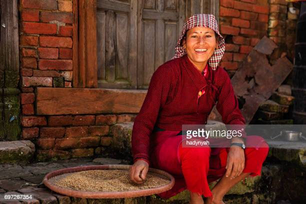 nepalese woman sifting a rice, bhaktapur - nepalese ethnicity stock pictures, royalty-free photos & images