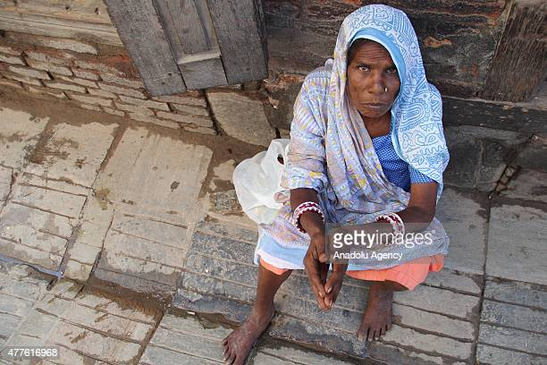 Nepalese woman sits at Durbar Square in Kathmandu Nepal on June 18 2015 Rubble of buildings hasn't been removed in some areas of Nepal after the...