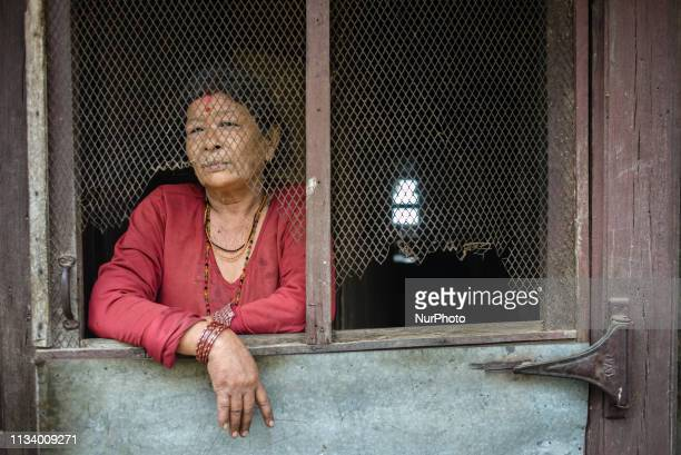Nepalese woman stands behind the door of her house in the old town of Bandipur Nepal on March 31 2019