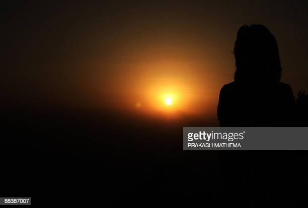 A Nepalese woman views a sunrise from Nagarkot some 30 kilometres northeast of Kathmandu valley on June 10 2009 Nagarkot is a popular hill...