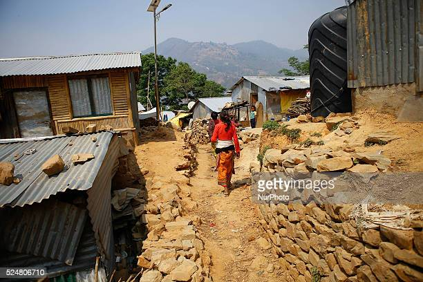 A Nepalese woman walks pass the temporary shift in Majuwa village on the outskirts of Kathmandu Nepal on April 26 2016 All most all the houses in the...