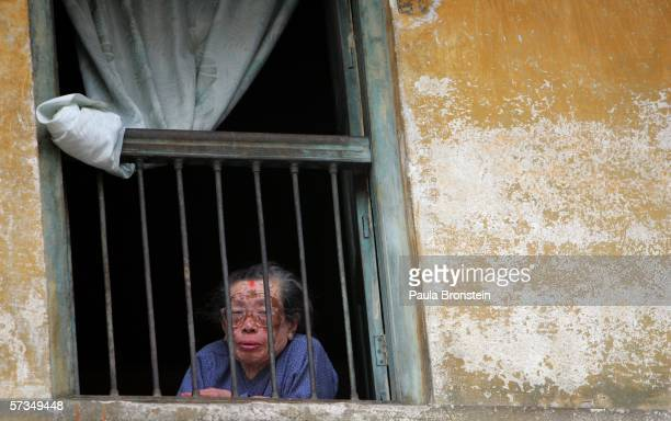 Nepalese woman watches a protest from her window as demonstrations continue against the rule of King Gyanendra April 17, 2006 in Kathmandu, Nepal....