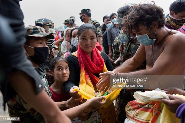Nepalese women and children receive food distributed by a nongovernment organization in the center of Kathmandu on April 30 2015 The UN launched an...