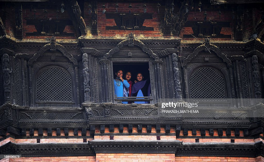 Nepalese women looks out from a window at Durbar museum in Kathmandu on April 4, 2013. The Durbar Square holds the palaces of the Malla and Shah kings who ruled over the city and isa UNESCO world heritage site located in the centre of the capital. AFP PHOTO/ Prakash MATHEMA