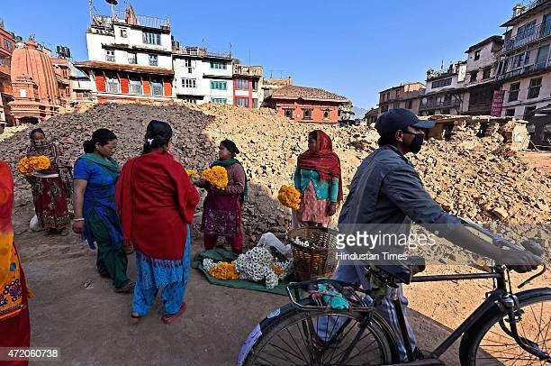 Nepalese women sell temple flowers in the backdrop of earthquake debris in Kathmandu Durbar Square complex, a week after earthquake, on May 3, 2015...